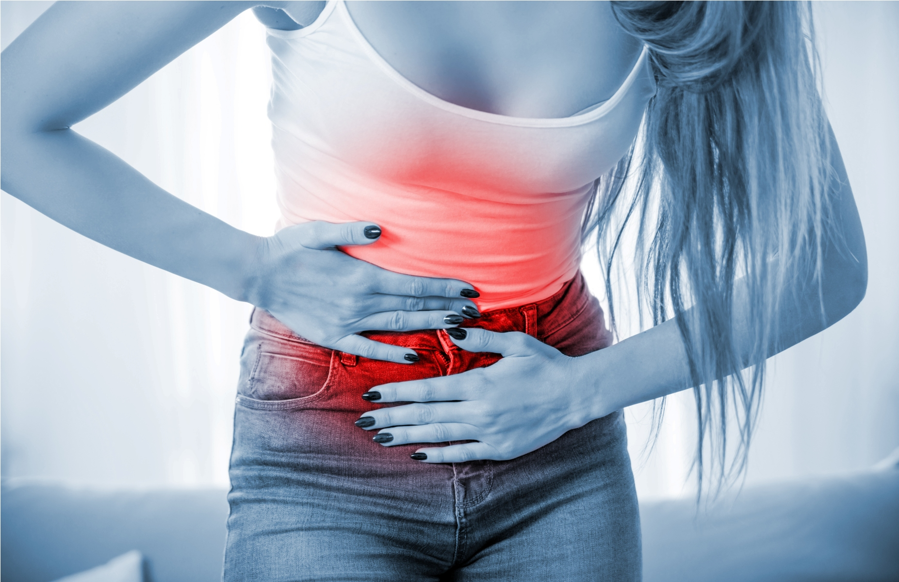 Young woman at home suffering from abdominal pain